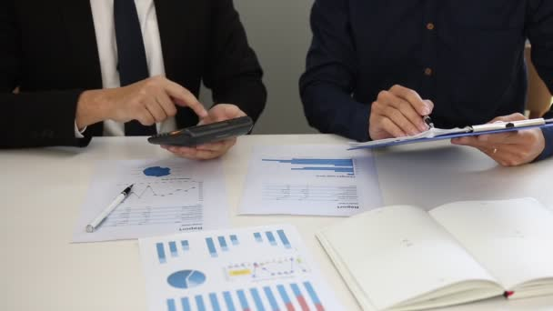 Managers and employees are calculating earnings on paper that contains graph data in the chart report and using calculators and collaboratively analyzing at the office.