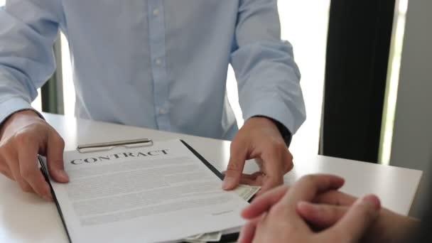 Zwei Geschäftsleute beim Händeschütteln, während ein Mann im Bürozimmer mit Korruptionskonzept Geld auf ein Dokument legt.