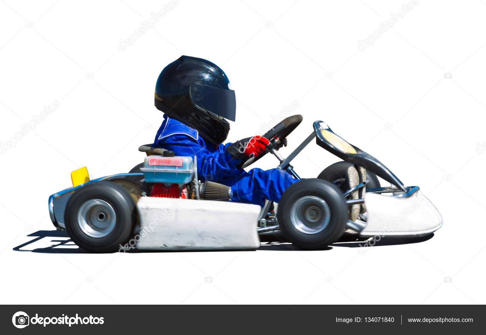 Young kid racing a go cart around a track. Panned to show speed ...