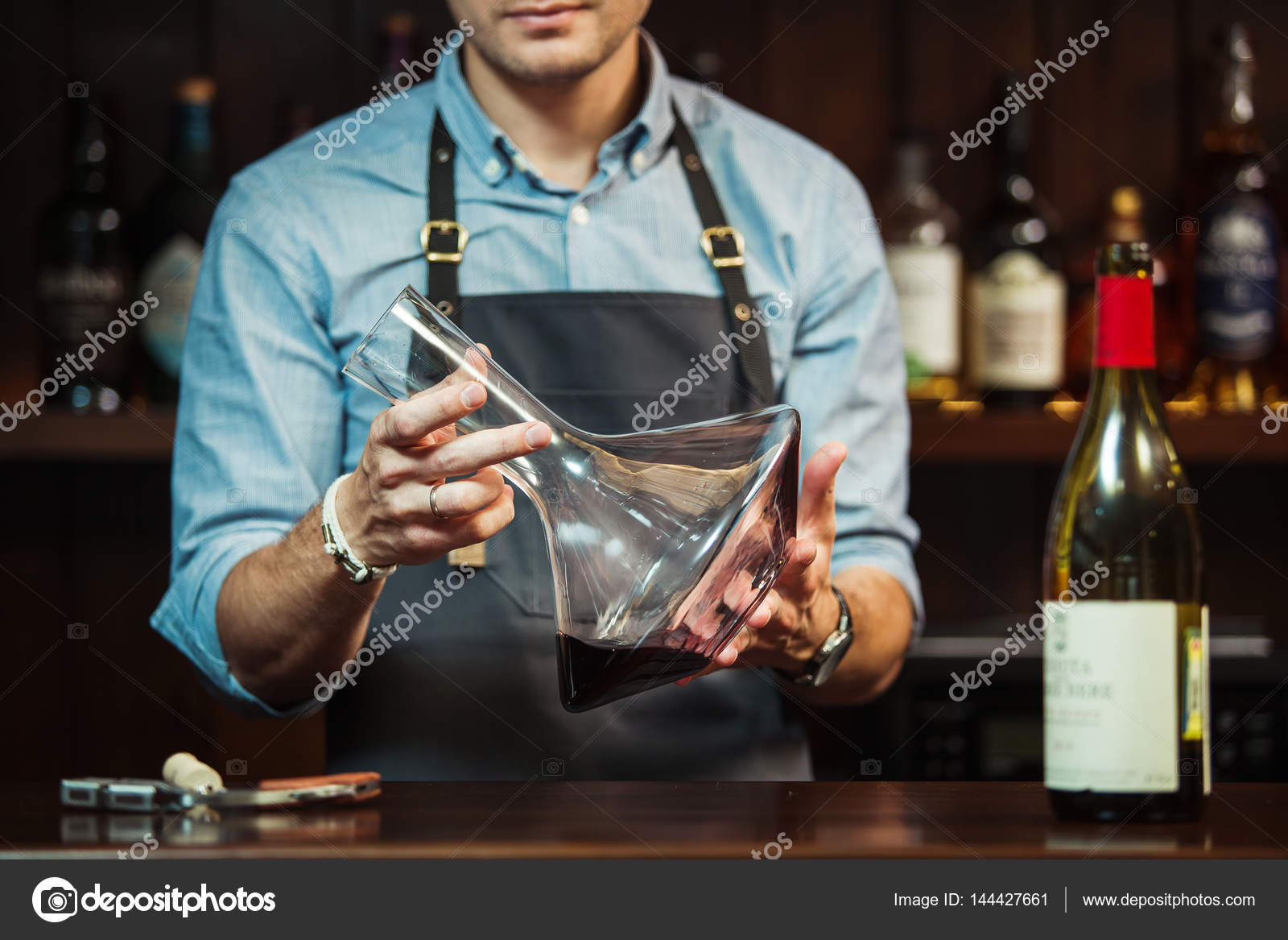 Weinglas am Tresen im Hintergrund der Sommelier mit Dekanter mit ...