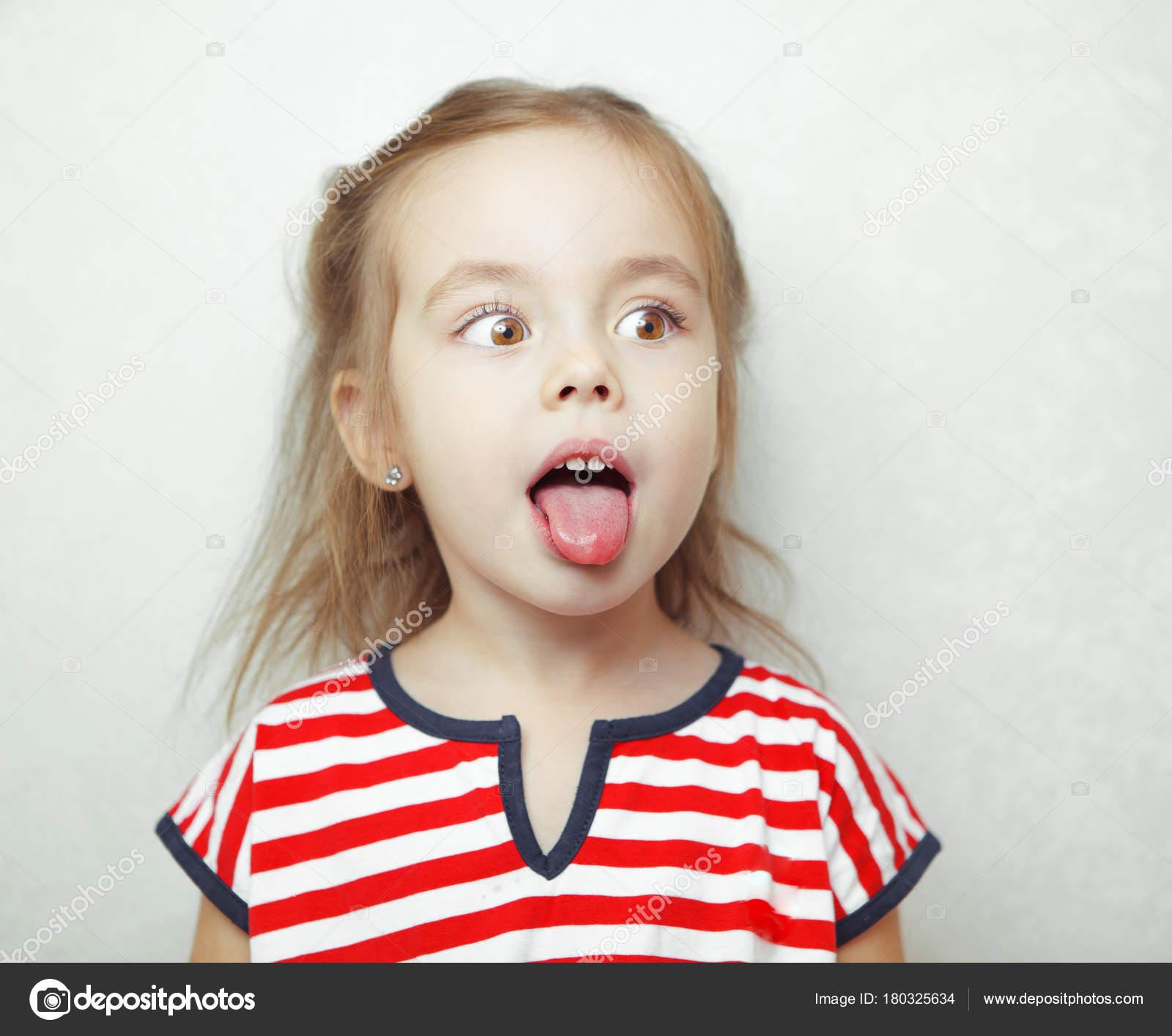 Adorablr kleines Mädchen zieht ihr die Zunge heraus und