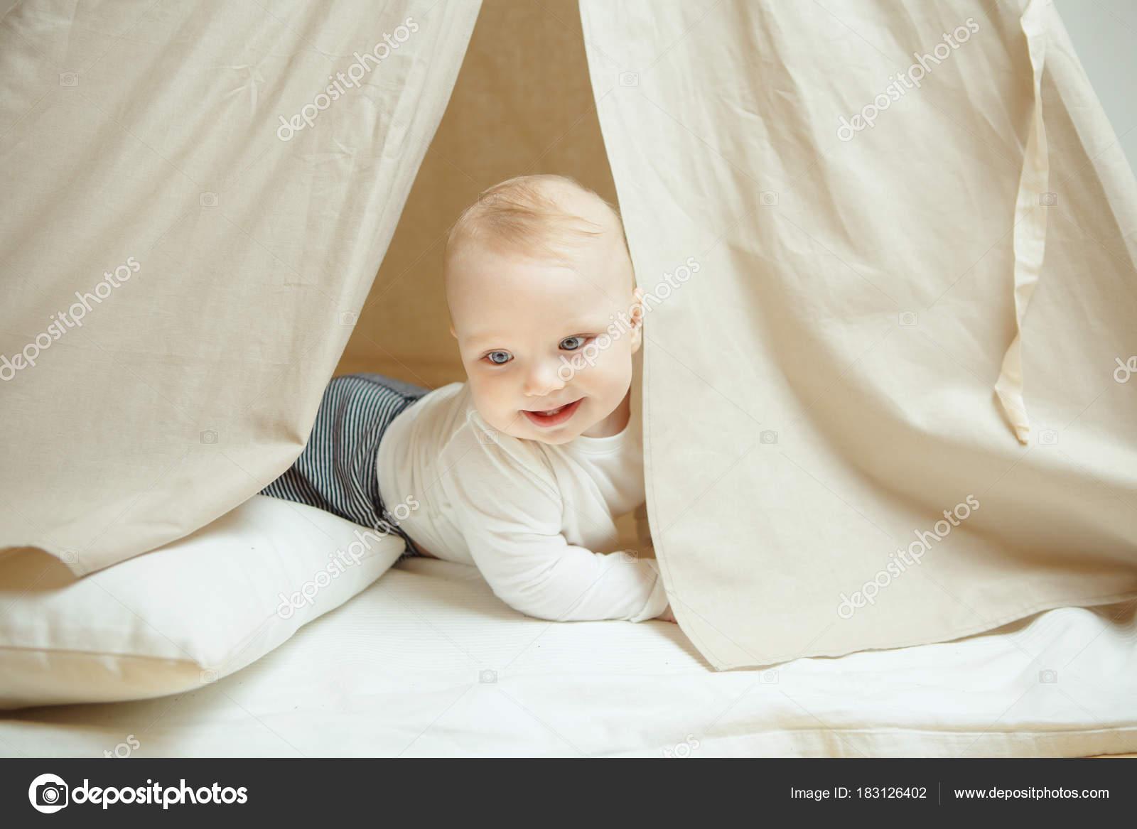 Bambino curioso guarda nella tenda per bambini con cuscino u2014 foto
