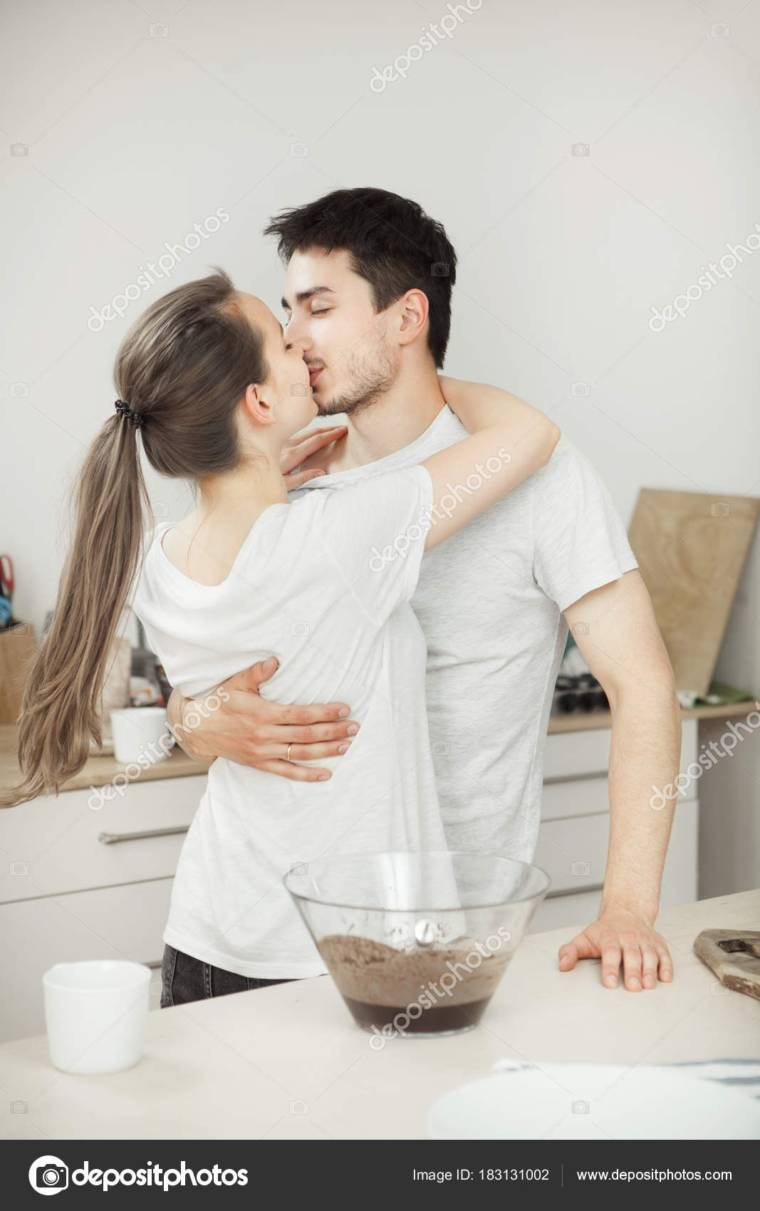Girl kisses her adorable husband in the kitchen. Romantic couple ...