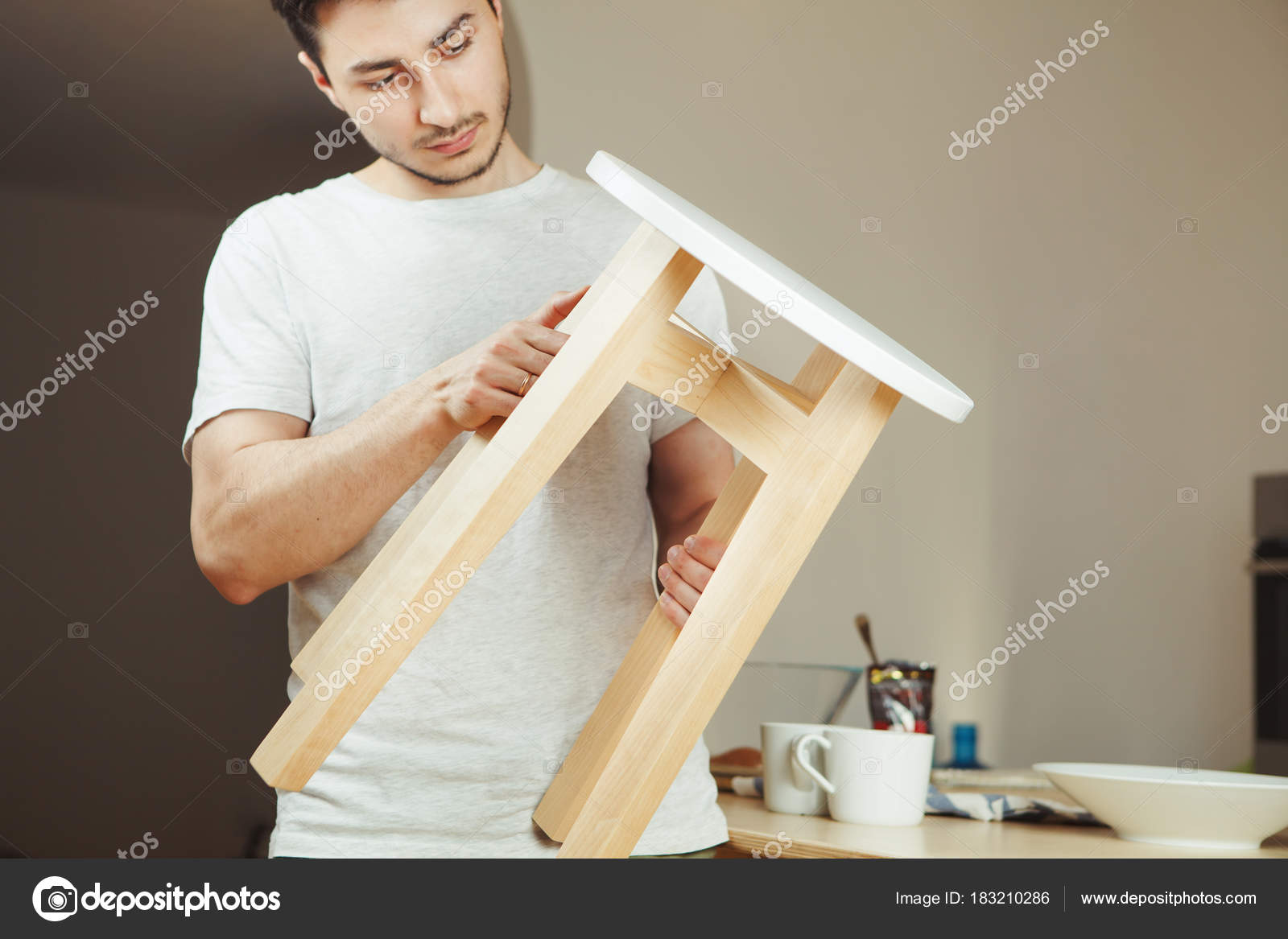 Pleasing Man Holding In Hands Wooden Stool Carefully Examining Seat Ocoug Best Dining Table And Chair Ideas Images Ocougorg