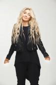 vertikální ženský portrét blonde v černých šatech, otravné zvedací ramena ze zoufalství nebo nevědomosti. zmatek, beznaděj, zoufalství