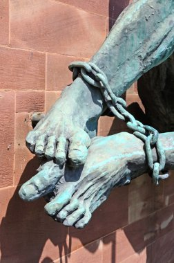 The Devils feet bound in chains (Michael and the Devil) on the wall of the new Cathedral, Coventry, UK.
