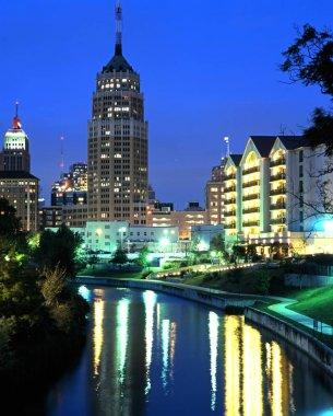 View along San Antonio River towards city buildings at night, San Antonio, USA.