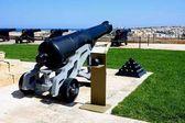 Děla v Upper Barrakka Gardens s výhledem přes přístav směrem k Vittoriose, Valletta, Malta