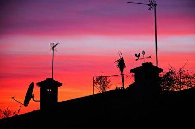 Mediterranean sunset over house rooftops, Spain.