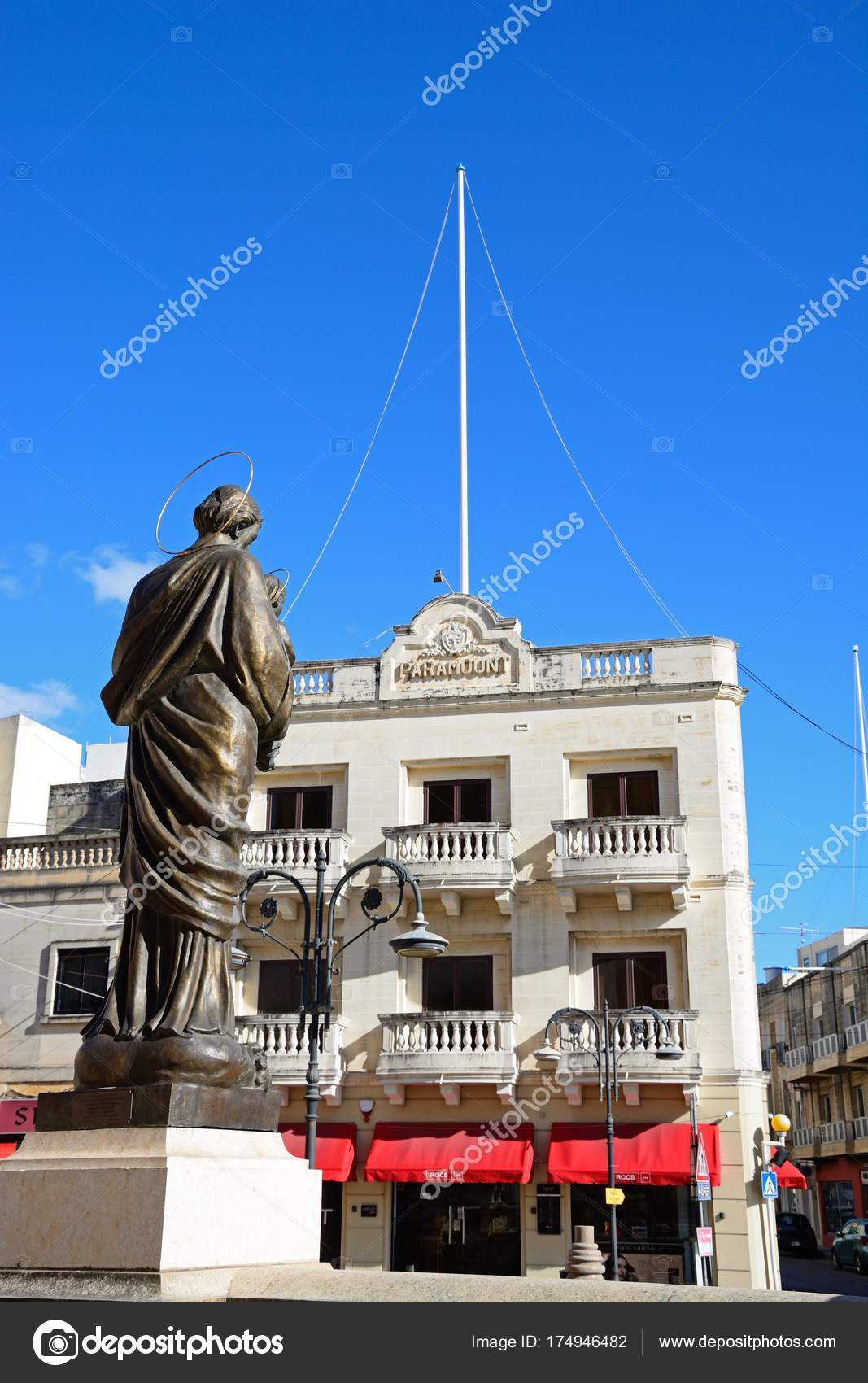 Statue In Front Of The Mosta Dome With The Old Paramount Cinema