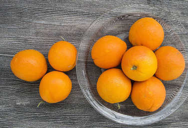 oranges in a glass bowl on a wooden floor,
