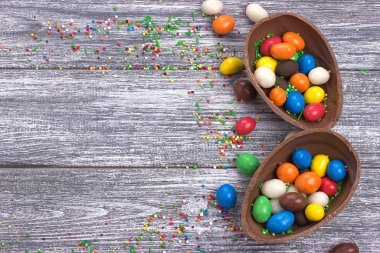Easter chocolate egg with colorful explosion of candies and sweets on gray colored wooden background.