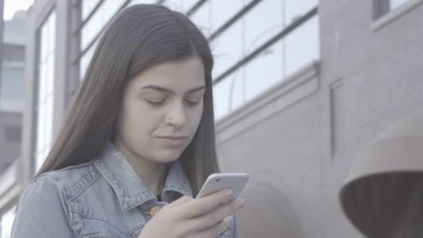 Atraktivní mladá žena pomocí dotykové obrazovky telefonu 4k