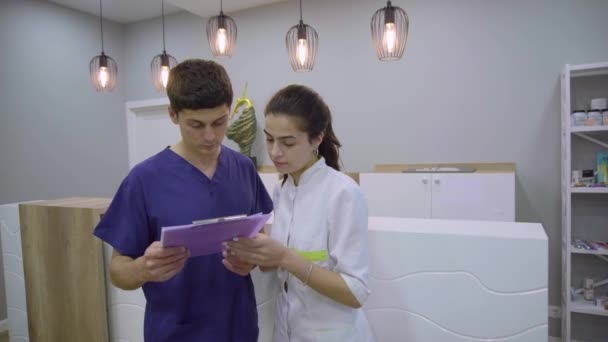 Mladá atraktivní mužských a ženských lékařů kontroly pacienta zdravotní průkaz