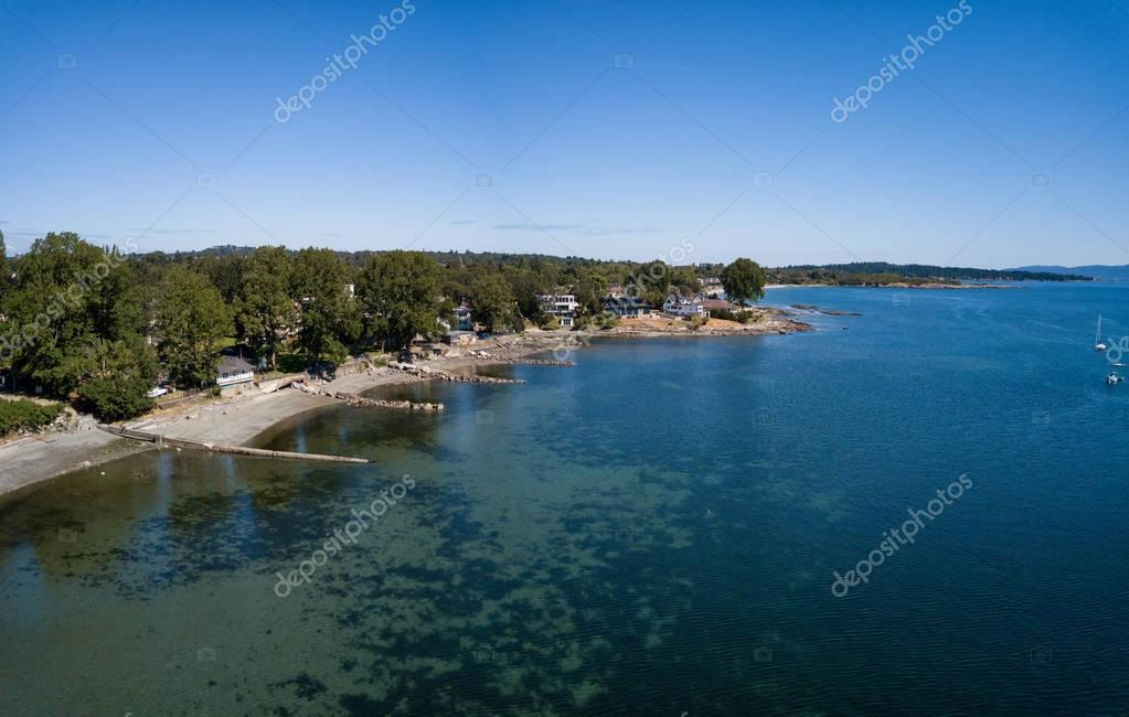 Aerial panoramic view of luxury homes in front of beautiful sandy beach on Pacific Coast. Taken in Victoria, Vancouver Island, British Columbia, Canada.