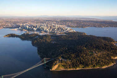 Beautiful Aerial View of Lions Gate Bridge, Stanley Park and Vancouver Downtown, British Columbia, Canada, during a bright spring sunset.