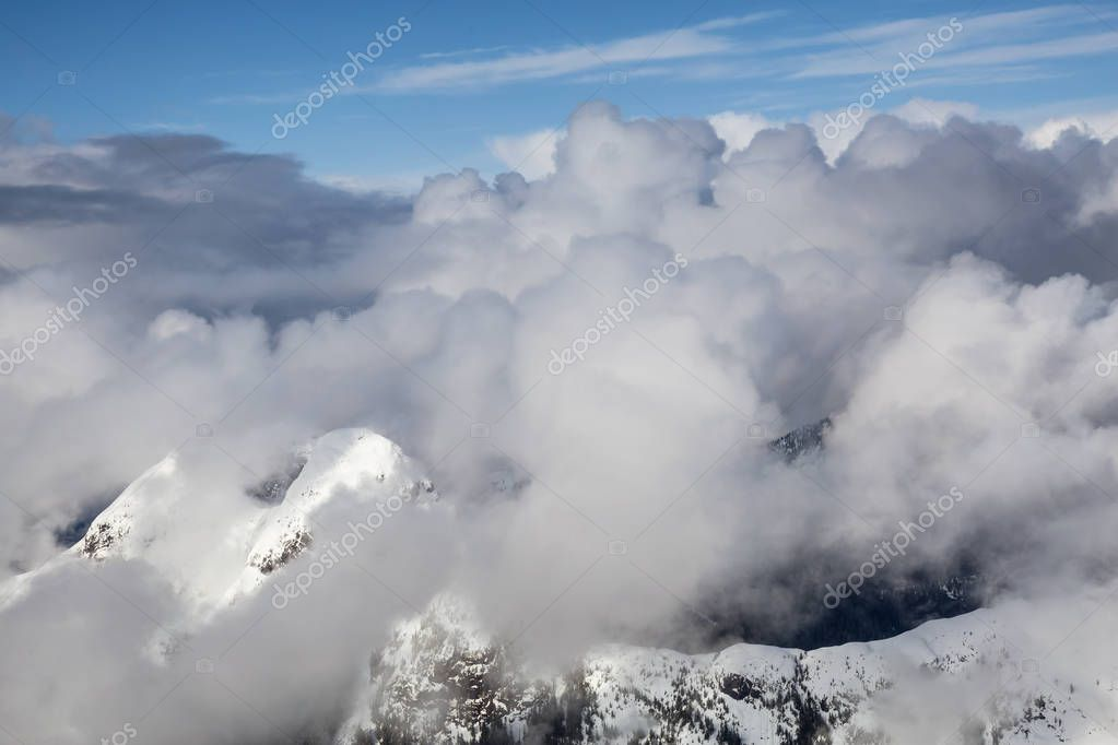 Aerial view on the mountain peaks covered in a thick layer of cumulus clouds during an evening. Taken north of Sunshine Coast, British Columbia, Canada.