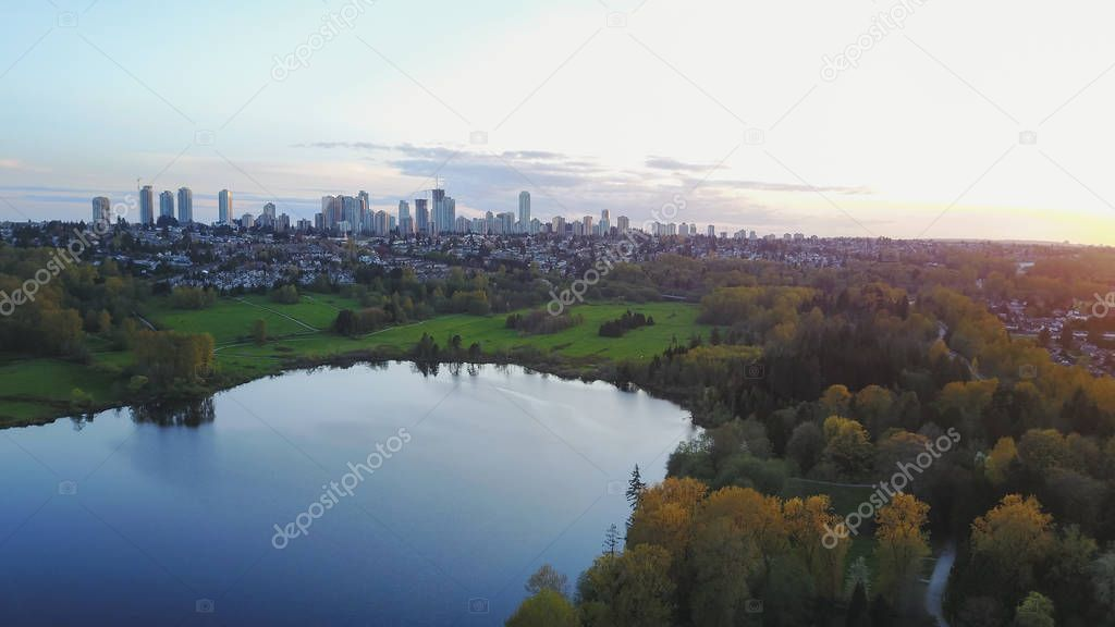 Beautiful Aerial View of Deer Lake in Burnaby, Greater Vancouver, British Columbia, Canada, with Metrotown City buildings in background. Taken during a colorful sunset.