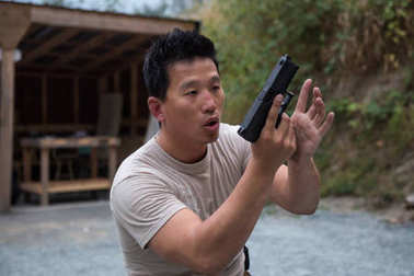 Asian young man is holding a gun in standing position aiming to shoot at a gun range