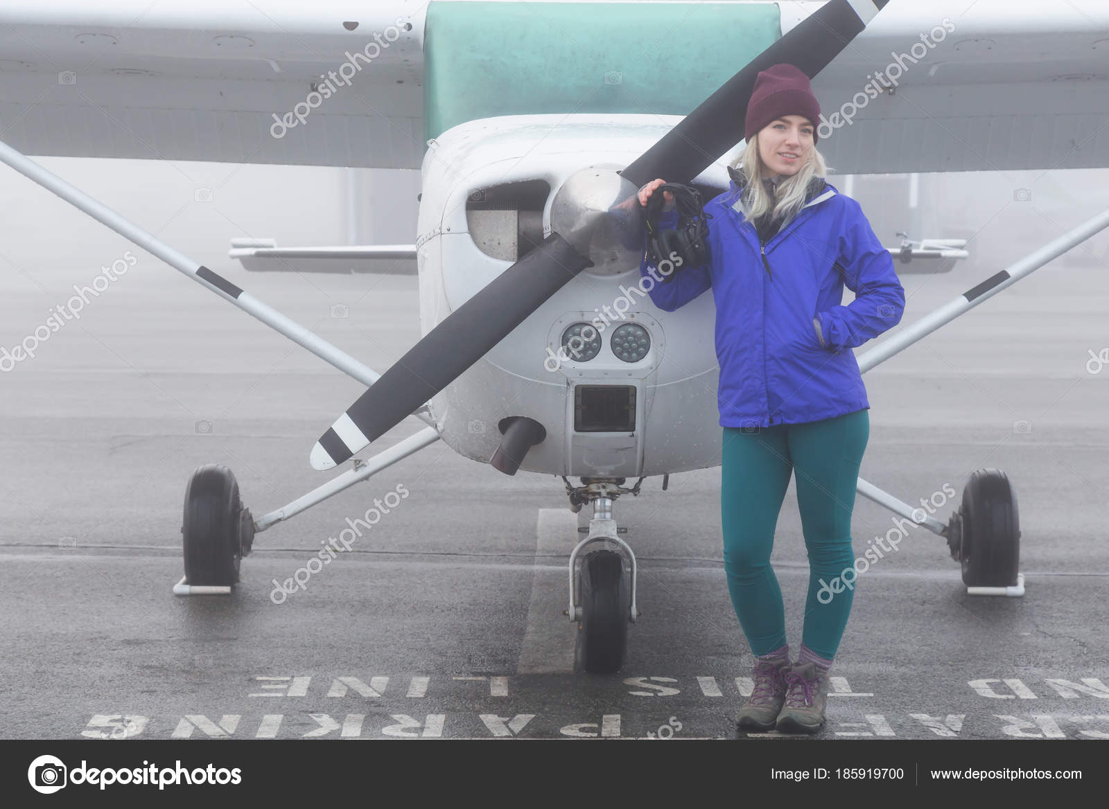 94a7c376c68 Mladý Student Pilot Kavkazský ženské stojí před jediného motoru letadla na  letišti. Během mlhavé zimní ráno v Pitt Meadows