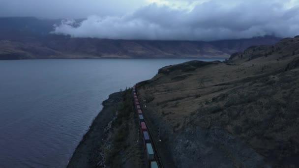 Letecká dron panoramatické krajiny pohled na křivky železnice a vlak u jezera během zatažené Podzimní slunce. Ve vnitrozemí Britská Kolumbie, Kanada