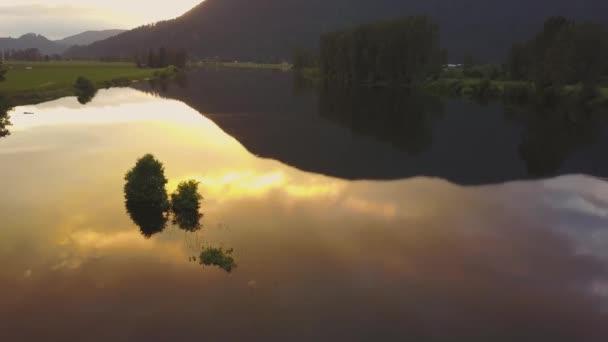 schöne Luftaufnahme des sumpfigen Sees mit Bäumen und einer bunten Reflexion der Wolken am Himmel während eines Frühlingssonnenuntergangs. in der nähe von mission, östlich von vancouver, britisch columbia, kanada.