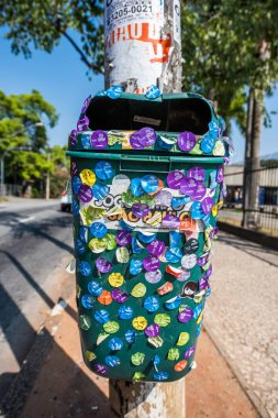 Garbage bin covered with stickers