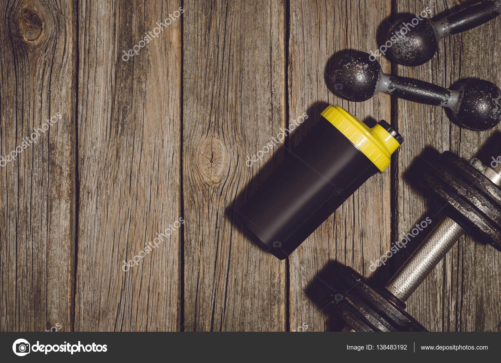 Alte Eisen Hanteln Oder Übung Gewichte Und Protein Shaker Flasche Auf Einem  Alten Holz Deck, Boden Oder Tisch In Der Turnhalle Im Freien.