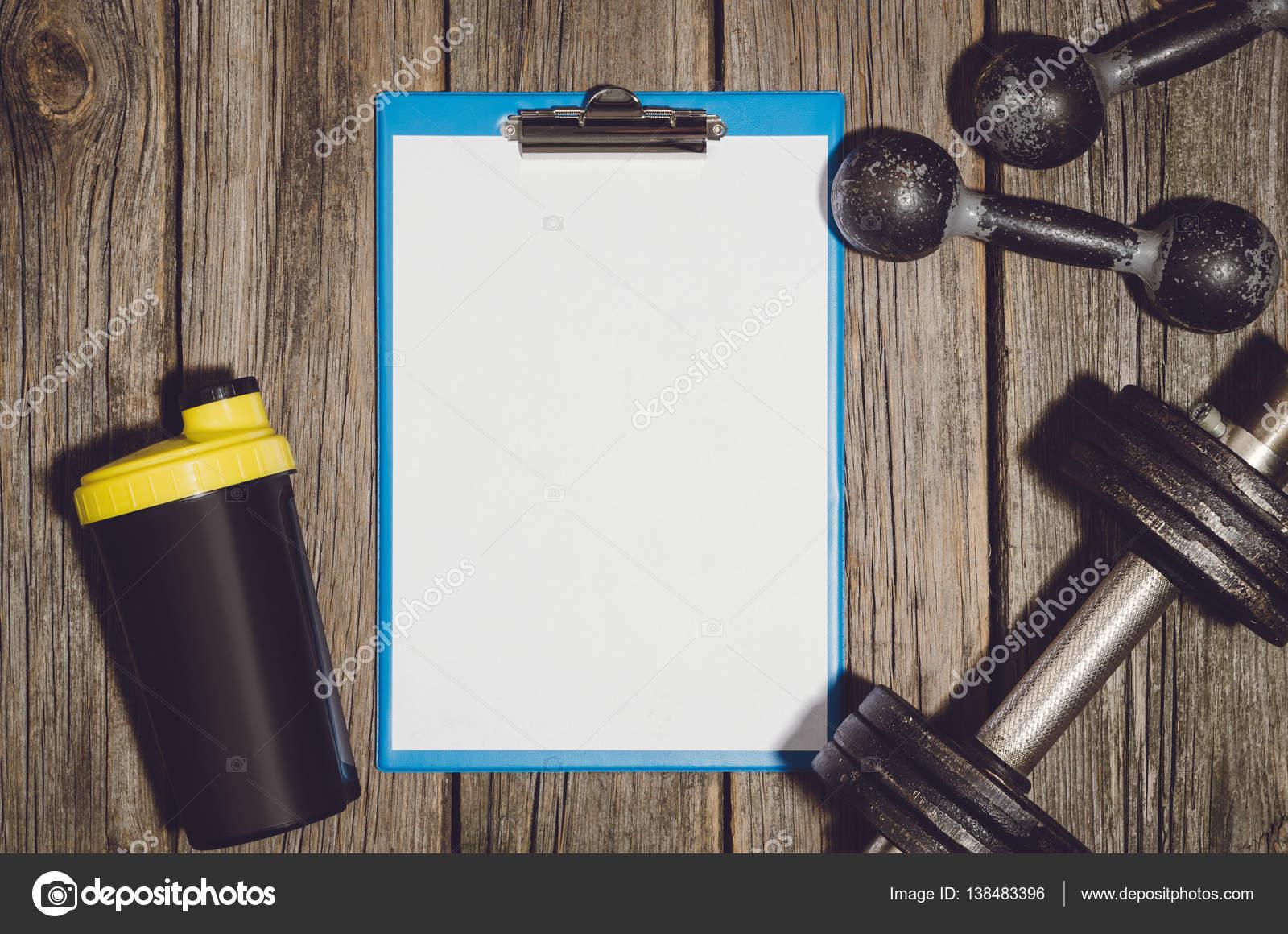 workout plan background dumbbells on wooden gym floor or