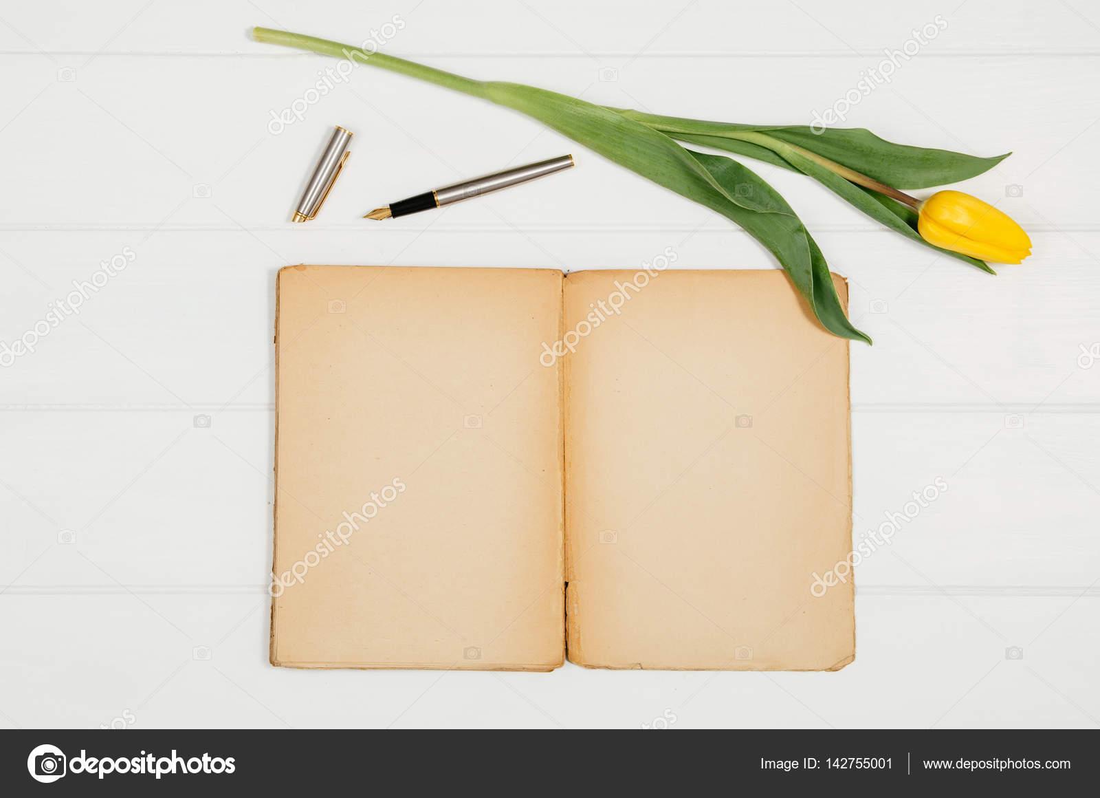 Sfondo con i tulipani gialli blocco note vuoto sulla tavola di