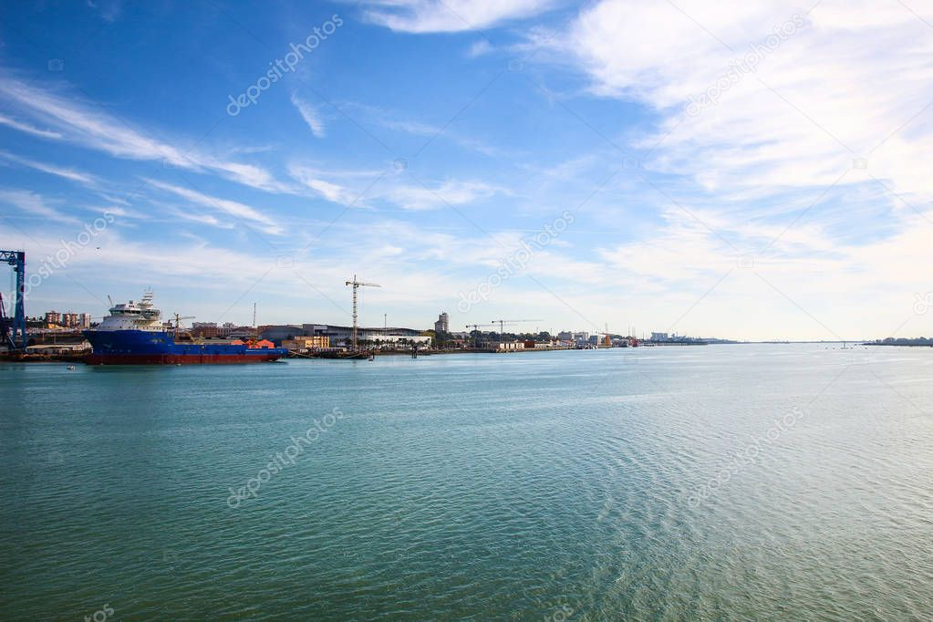 Landscape of port of Huelva with cranes, fishing boat in shipyard and mall in coast of Huelva, Andalusia, Spain.