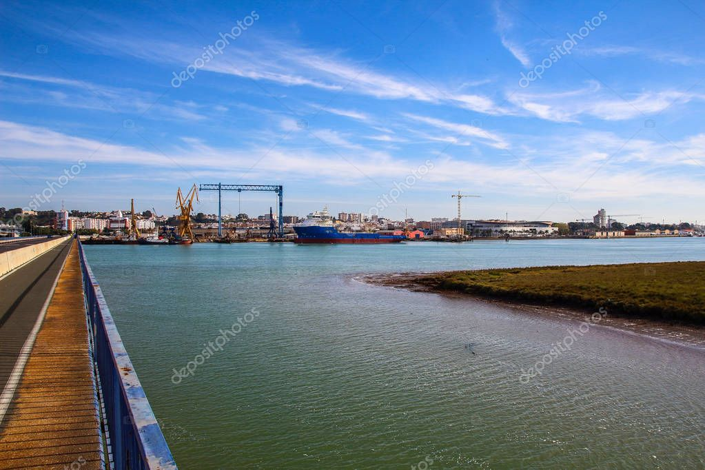 Beautiful landscape from bridge of cranes with big fishing boat in shipyard and full port of coast of Huelva, Andalusia, Spain.