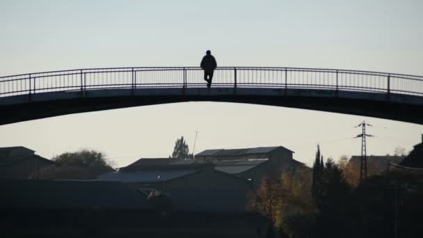 man standing on the bridge and the town in the background