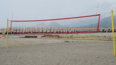 Volleyball court on the beach, people passing by