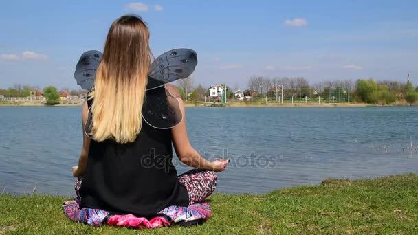 Mädchen mit Schmetterlingsflügeln meditieren im Lotus-Position neben dem ruhigen Wasser