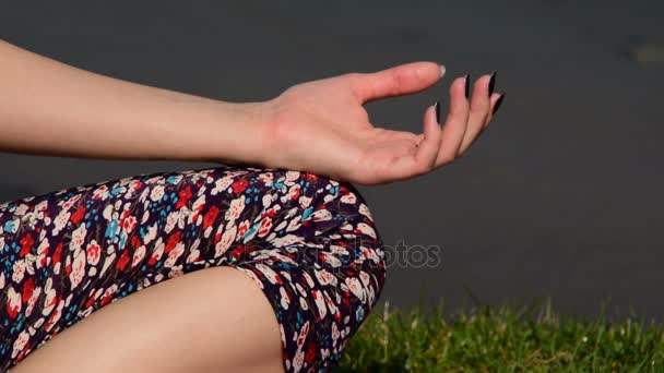 female hand in meditation position, leaning on one knee, lotus position
