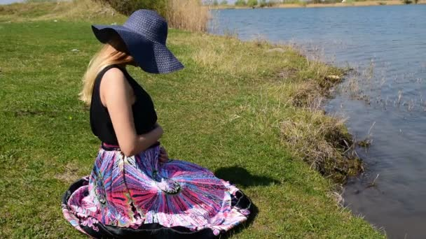 Pregnant girl sitting on the shore and holding her belly