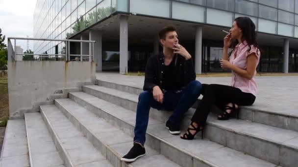 junger Mann und junge Frau sitzen auf der Treppe und rauchen Zigaretten