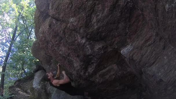 mladší muž šplhá ke skále bez horolezecké vybavení, volné sólové lezení