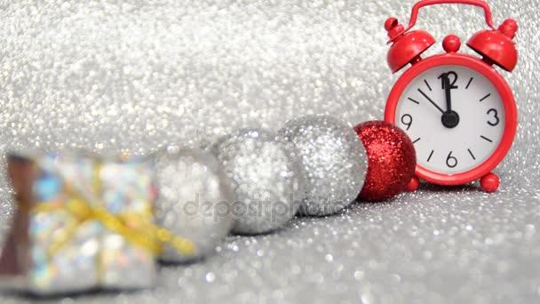 die rote Abenduhr zählt 10 Sekunden bis Mitternacht, ein frohes neues Jahr, ein Geschenk und silberne Neujahrskugeln
