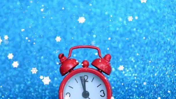 červené hodiny rychle odráží posledních 5 minut v roce, šťastný nový rok, na modrém pozadí a sněhová vločka