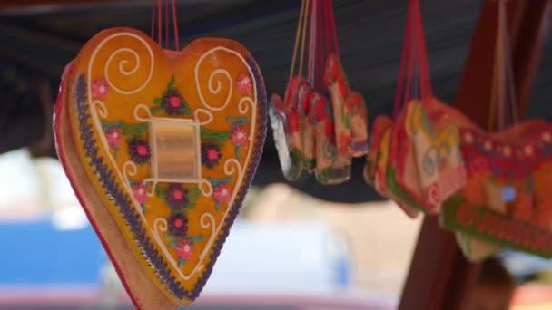 Licitars szív és mézeskalács alakú ló lóg az ünnepi sátor alatt. Édességek zsákokban egy utcai vásáron.