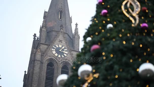Rozmazané vánoční strom vánoční koule a věnec světel bokeh zajiskřilo, s horní části gotický cihlový kostel a zlaté hodiny na střeše na pozadí