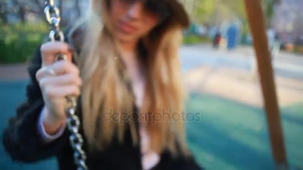 Detailní záběr na atraktivní mladá žena nosí stylové oblečení, houpání na houpačce venku. Roztomilá studentka s dlouhé blond vlasy, baví se během jarních prázdnin. Student na dovolené