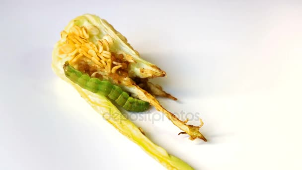 Pie de Caterpillar en un pedazo de pimienta sobre fondo blanco
