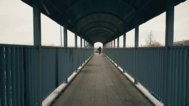 Man running away through the footbridge