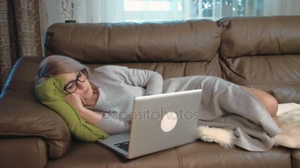 Young woman using her laptop feeling sleepy