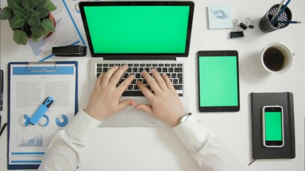 Draufsicht Geschäftsmann arbeiten am Laptop am Schreibtisch mit mehreren Greenscreen Gadgets Handy und tablet