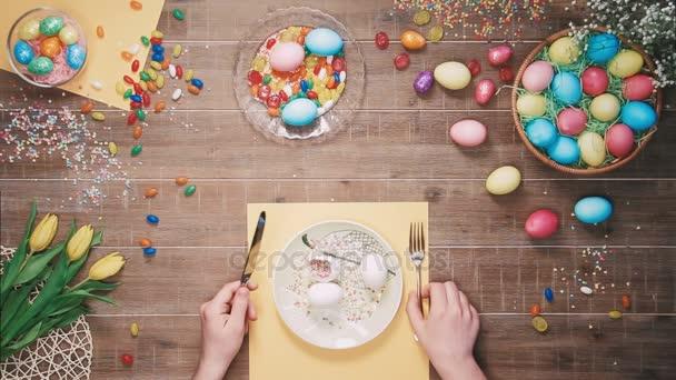Ember tartja a kést és a villát előtt lemez húsvéti tojás húsvéti tojás díszített asztalon. Szemközti nézet