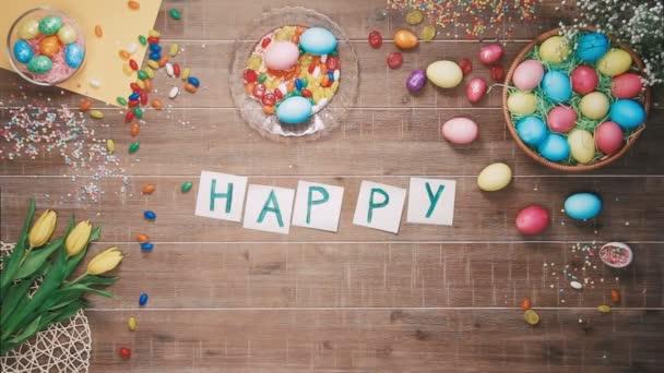 Man setze Wörter Frohe Ostern auf Tisch mit Ostereiern dekoriert. Ansicht von oben